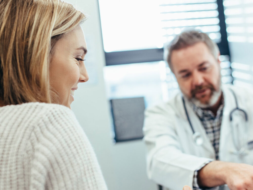 A female patient going over medical results at an in-person appointment with a male physician.