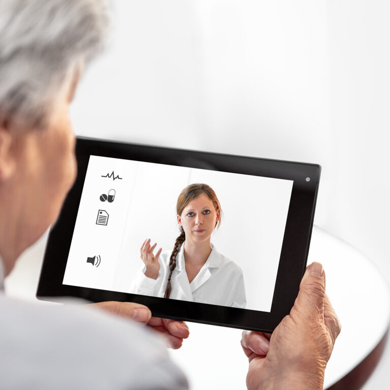 A senior citizen holds a tablet during an online doctor visit.